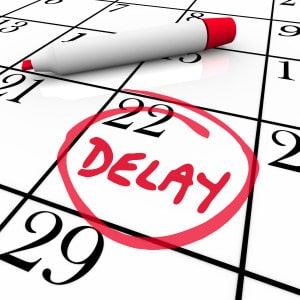 Delay word circled on a day or date on a calendar or schedule to illustrate a trip, meeting or appointment that has been pushed back
